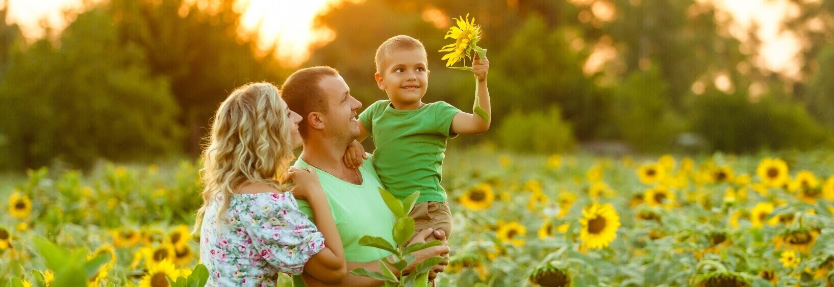 mother and father holding son and smiling in sunflower field